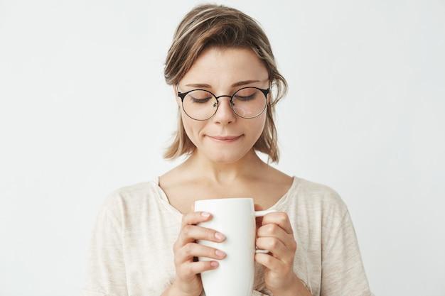 Красивая нежная девушка в очках, держа чашку, глядя вниз.