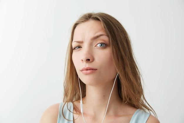Молодая красивая девушка поднять лоб, слушать потоковую музыку в наушниках.