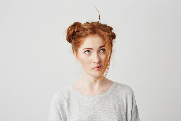 甘やかされて育った髪のお団子を持つ美しい赤毛の若い女の子の肖像画。