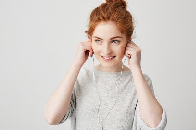 ヘッドフォンを入れて笑っている陽気な赤毛の若い女の子の肖像画。