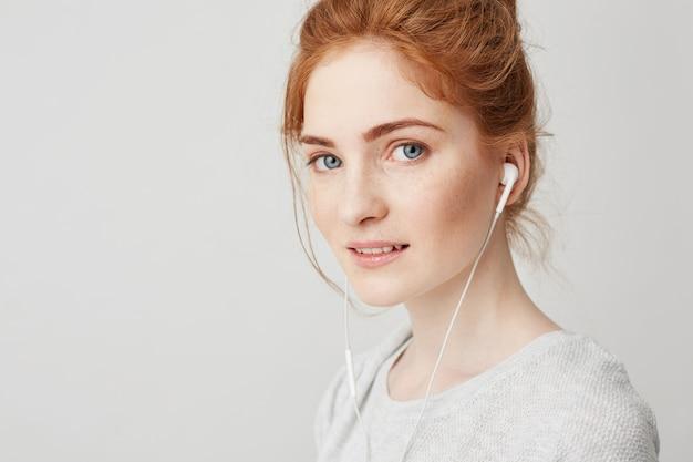 笑みを浮かべてヘッドフォンで青い目を持つ若い美しい優しい赤毛の女の子の肖像画。