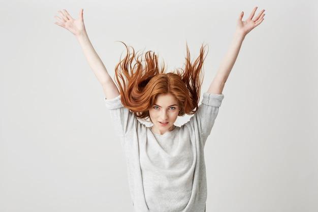 Портрет молодой веселый красивый рыжий девушка улыбается, пожимая волосы.
