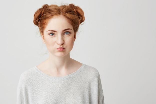 Портрет молодой довольно рыжая девушка делает смешное лицо.