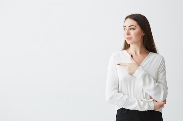 若い美しいブルネットの実業家側で人差し指を見て笑っています。