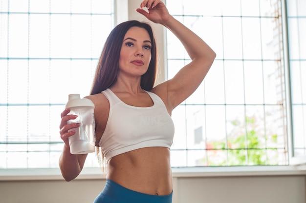 Фитнес-инструктор в спортивной комнате питьевой воды