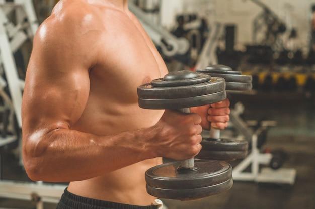 スポーツルームのバックグラウンドでフィットネスインストラクター。筋肉のフィット感とスリムなボディを持つ男性モデル。スポーツコンセプト