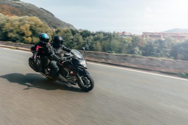 バイクで道を旅する未知のバイカーカップル