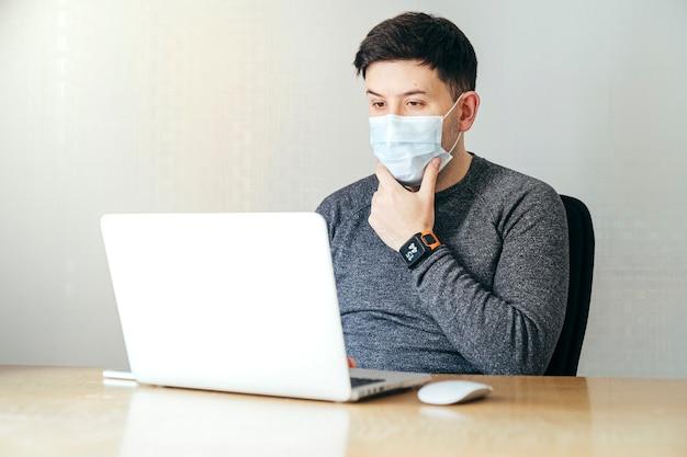 孤立した若い男がマスクと灰色のジャージを着ての側面図です。彼はラップトップの前にいます。ノートパソコンを見ながら、彼はあごに触れています。彼は木のテーブルの上で働いています。