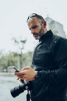 スマートフォンを使用して、雨の下でもう一方の手でカメラを保持している男。