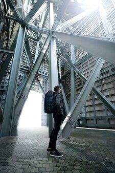 Молодой человек смотря вверх под стальной структурой. он одет в черную одежду. он носит черный рюкзак с оранжевыми деталями. он бородатый. вид сзади. концепция городского исследователя
