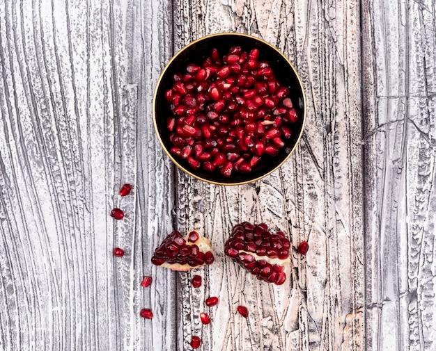 木製テーブルの上のプレートトップビューでザクロの種子