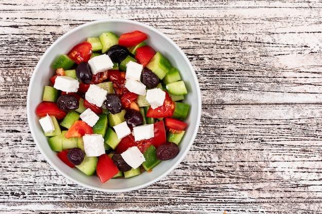 Салат с сыром оливковое огурцы помидор в миску белого на деревянный стол