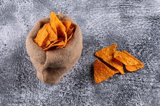 Вид сбоку чипсы в льняной сумке горизонтальные