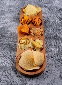 Чипсы на деревянной тарелке вертикальные