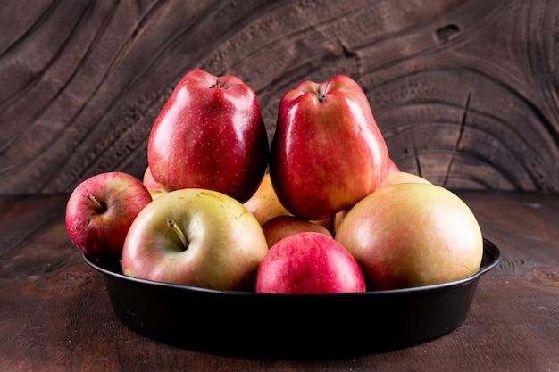 Вид сбоку красные яблоки в черном металлическом подносе