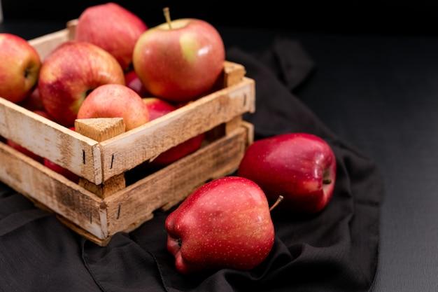 Вид сбоку красные яблоки в ящике с черной тканью
