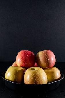 Вид сбоку мокрые яблоки в металлическом подносе на черном