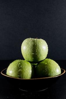 Вид сбоку мокрые зеленые яблоки в миске