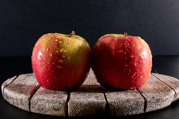 Вид сбоку мокрые красные яблоки на белой деревянной доске на черном горизонтальном