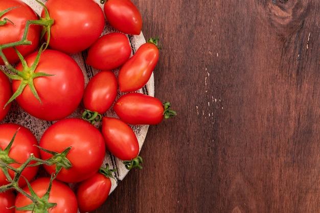 Помидоры и помидоры черри на деревянной доске текстуры