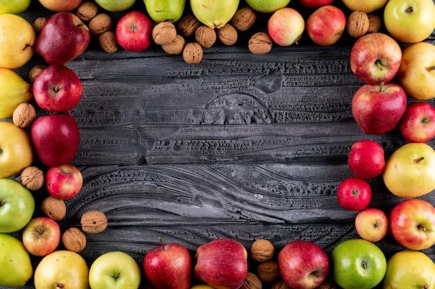Вид сверху яблоки и груши с орехами и грецкими орехами с копией пространства на серой деревянной горизонтали
