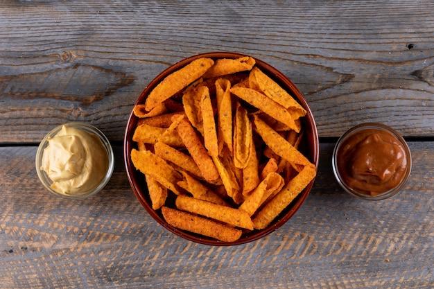 Вид сверху чипсы с соусами в мисках на коричневой деревянной горизонтали