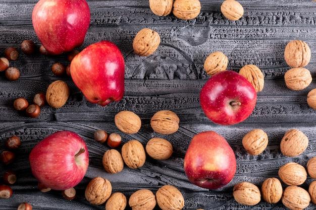 Вид сверху красные яблоки с грецкими орехами на серой деревянной горизонтали
