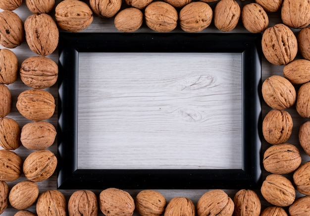 Вид сверху грецкие орехи с копией пространства в черной рамке в путанице на белом деревянные горизонтальные