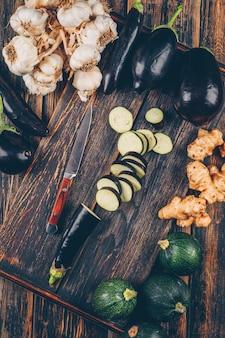 Плоские кладут нарезанные баклажаны на разделочную доску с цуккини, чесноком, имбирем вокруг на деревянный стол.