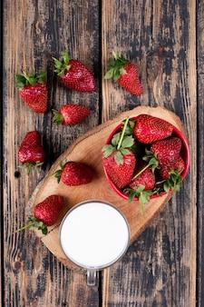 スタブと木製のテーブルの上にミルクのカップとボウルと周りのイチゴ。