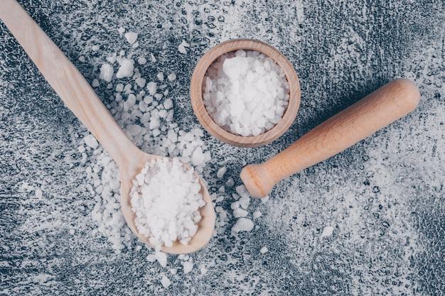 Морская соль в миске и ложке со скалкой