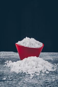 Морская соль в красной миске и вокруг