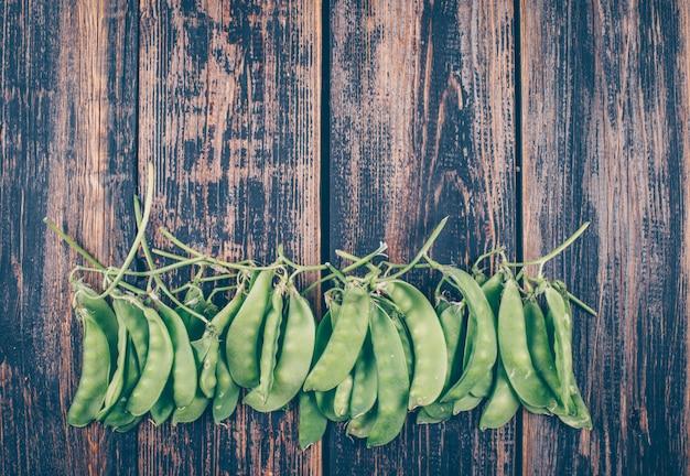 暗い木製のテーブルに並んでいるフラットレイアウト新鮮なエンドウ豆