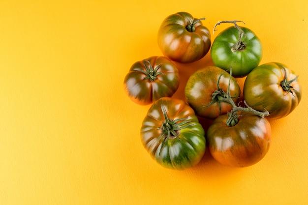 黄色の表面にコピースペースを持つフレームの左側にある緑のトマト