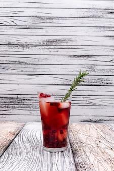 Гранатовый сок в стакан с кубиками льда на деревянный стол