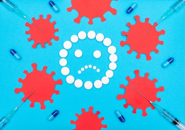 Рядом вирус и таблетки, образующие грустные эмодзи с иглами и таблетками