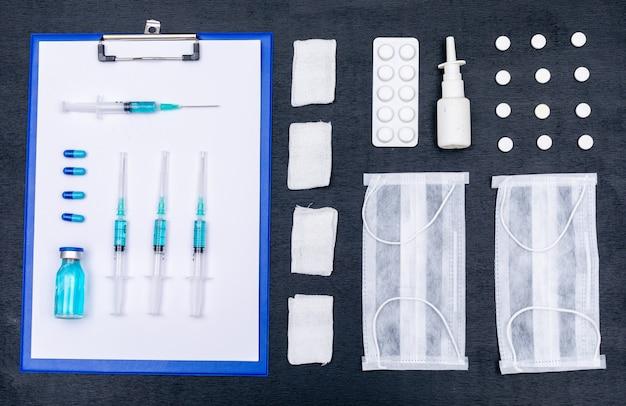 Вид сверху таблетки, маски, иглы, лекарства с держателем для бумаги, спреем для носа и повязкой