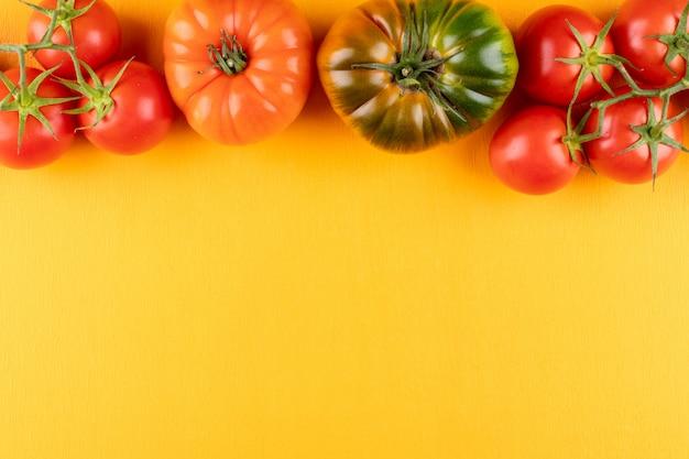 黄色の表面のフレームの上部にあるトマト