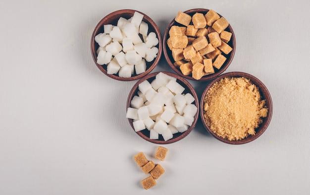 Белый и коричневый сахар в мисках. вид сверху.