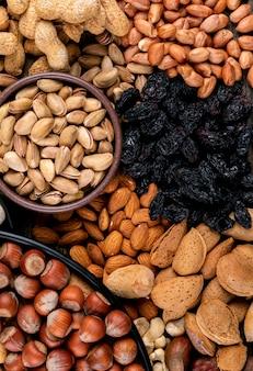 Высокий угол зрения ассорти орехи и сухофрукты в разных мисках с пекан, фисташки, миндаль, арахис, кешью, кедровые орехи. вертикальный