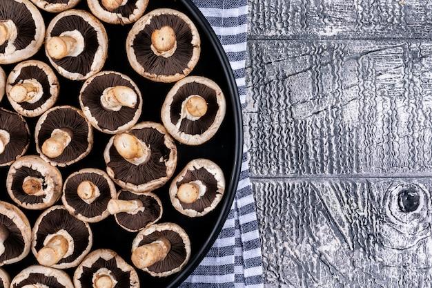 Несколько перевернутых грибов на сковороде, на скатерти, серый деревянный стол