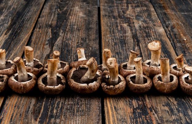 暗い木製のテーブルにいくつかの反転キノコ