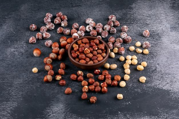 Очищенные и очищенные от скорлупы лесные орехи в коричневой миске под высоким углом на темном каменном столе