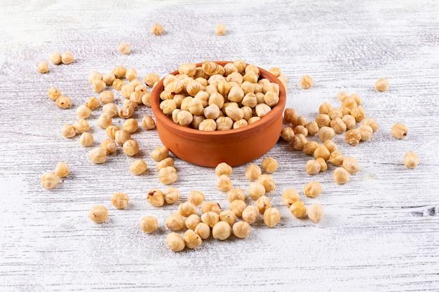 Очищенные орехи в коричневом шаре под высоким углом зрения на белом деревянном столе