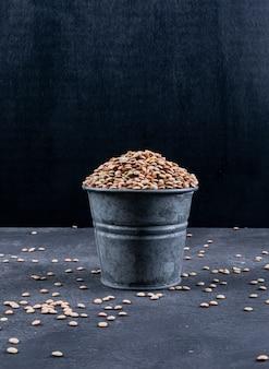 黒い石のテーブルに黒いミニバケツに緑のレンズ豆。側面図。