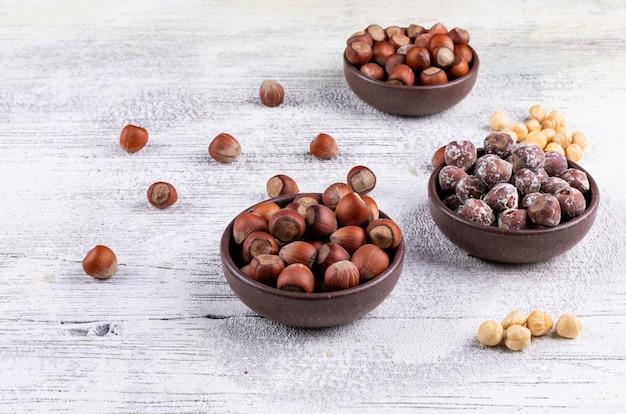 Лещинные орехи в миску с высоким углом очищенных фундука очищенный вид на белый деревянный стол