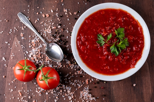 木製の表面に塩トップビューでトマトパスタスープ