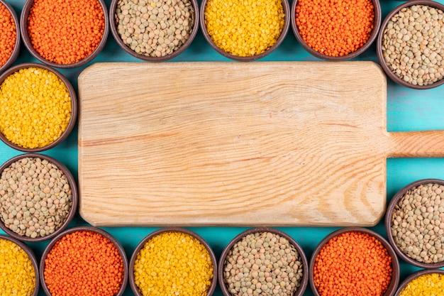 木製のまな板とボウルに赤と黄色のレンズ豆