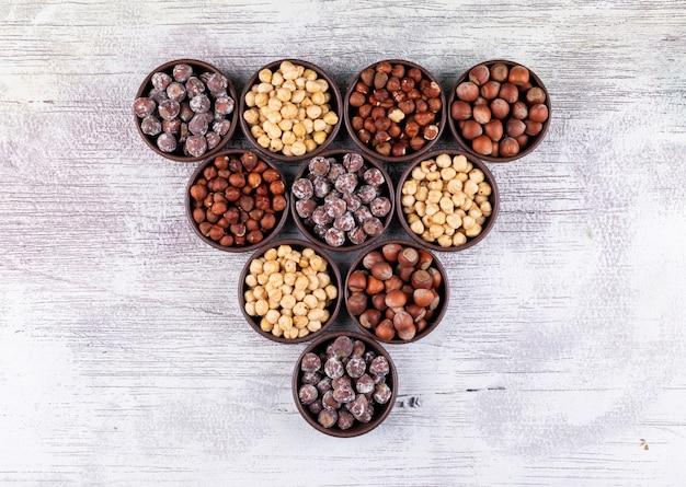 Орехи взгляд сверху различные в коричневых шарах с обстреливаемыми, очищенными фундуками на белом деревянном столе. горизонтальный