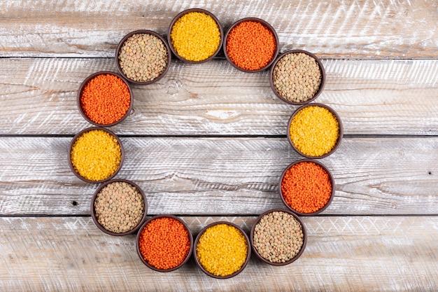 ベージュの木製のテーブルの上に茶色のボウルで黄色、赤、緑のレンズ豆を平面図します。